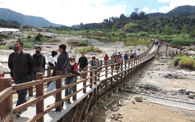 Tourists walking on wooden bridge in Banjarnegara Indonesia